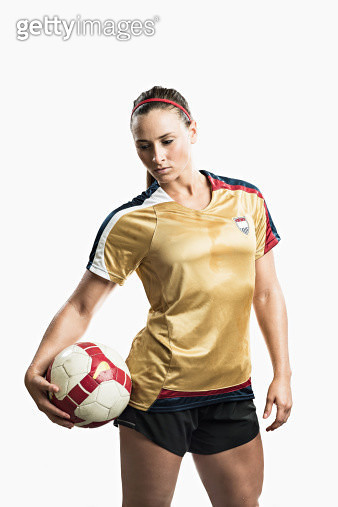 Studio shot of young female soccer player holding ball - gettyimageskorea