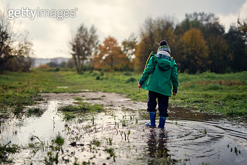 Lone little boy walking in puddle on autumn day - gettyimageskorea