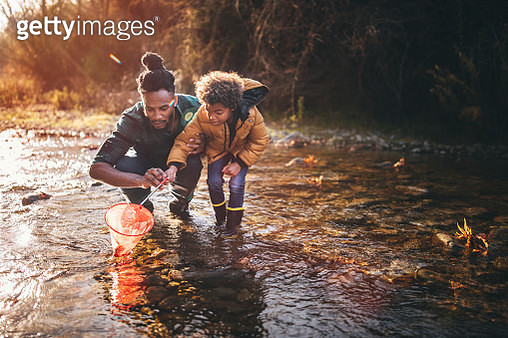Father and son fishing with fishing net in river - gettyimageskorea