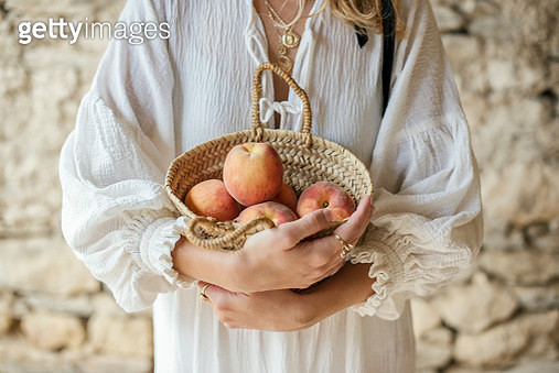 Woman holding reusable bag full of organic peaches - gettyimageskorea