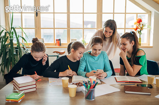 Private teacher and group of teenage girls using phones while doing homework - gettyimageskorea