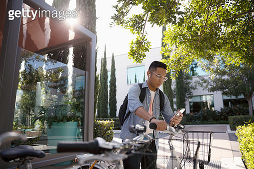 Young man with bicycle using smart phone on sidewalk - gettyimageskorea