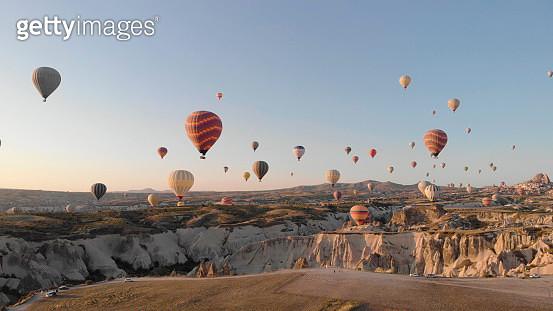 Hot air balloons rise above desert landscape - gettyimageskorea