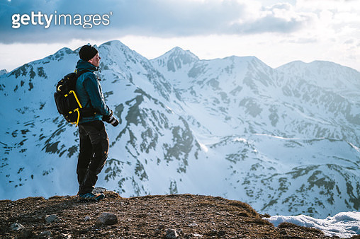 Snow capped mountains distant; snowy terrain in foreground - gettyimageskorea