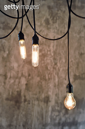 Hanging light bulbs against a concrete wall - gettyimageskorea