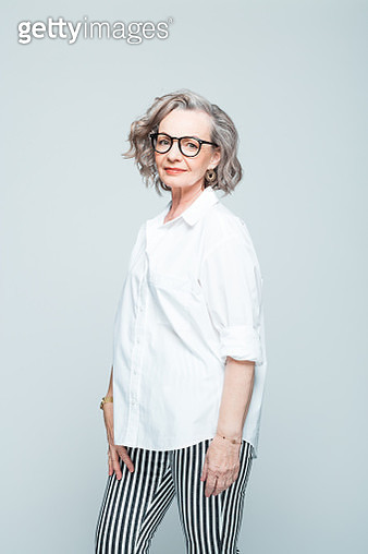 Elderly lady wearing white shirt, striped trousers and glasses standing against grey background, smiling at camera. Studio shot of female designer. - gettyimageskorea