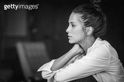 Black and white, close-up beauty portrait of a pensive young woman in white shirt. The woman has brown eyes, healthy clean skin, natural make-up and dark hair that is swept back from her face. Her head is slightly leaned on her hand. The shot is executed  - gettyimageskorea