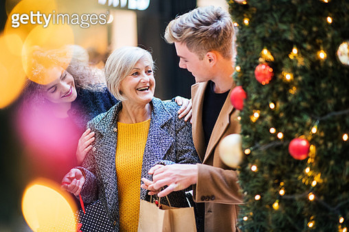 A Portrait Of Grandmother And Teenage Grandchildren In Shopping Center At Christmas. - gettyimageskorea