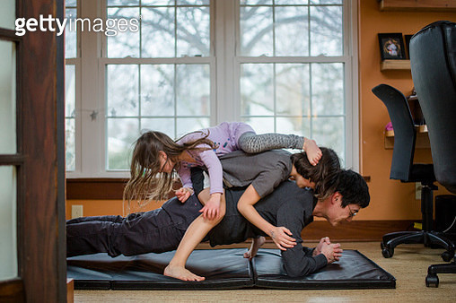 A father holds a plank position with two children piled on his back - gettyimageskorea