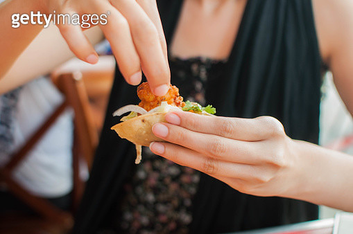 A young woman is eating a freshly made shrimp fajita - gettyimageskorea