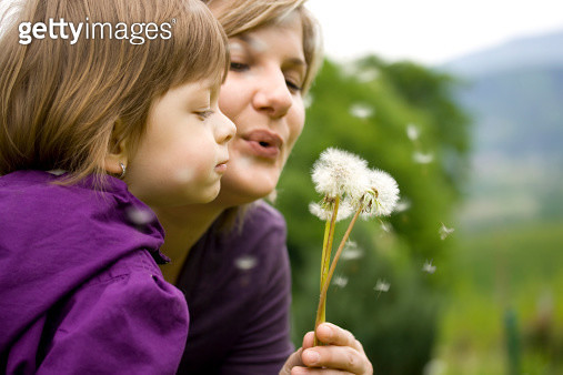 Mother and child blowing dandelion - gettyimageskorea