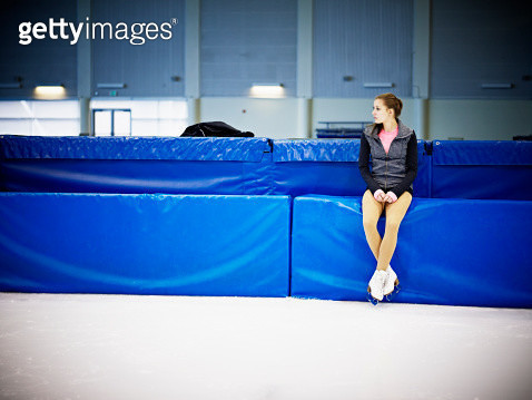 Female figure skater sitting on pad on ice rink - gettyimageskorea
