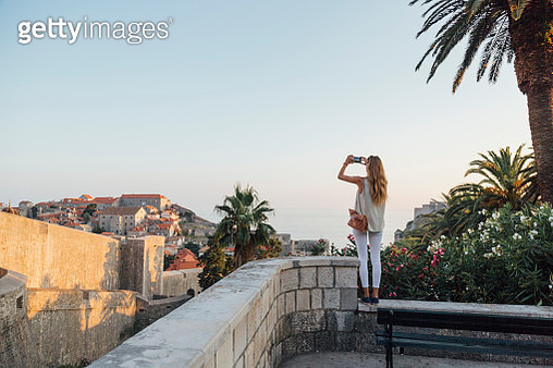 Caucasian woman standing on park wall photographing cityscape - gettyimageskorea