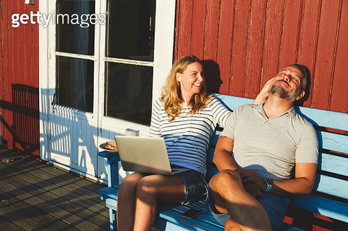 Happy woman using laptop while playing with man on bench at porch during summer - gettyimageskorea