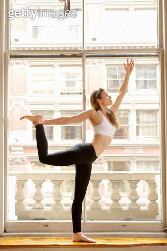 Woman doing dancer pose by window - gettyimageskorea