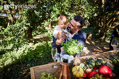 Mature man holding baby on a garden party - gettyimageskorea
