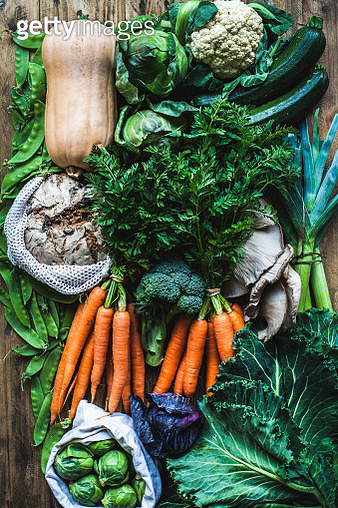 A flatlay of fresh vegetables, mushrooms and bread from a farmer's market, using cloth bags instead of plastic. A zero waste weekly shop for a couple who eat a lot of vegetables. - gettyimageskorea