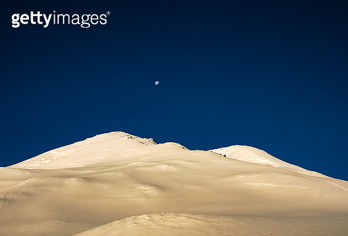 Low Angle View Of Snowcapped Mountain Against Blue Sky - gettyimageskorea