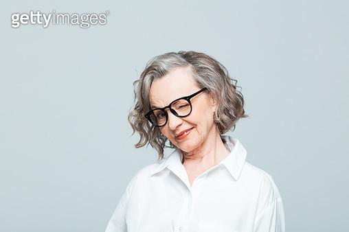 Elderly lady wearing white shirt and glasses standing against grey background, blinking an eye. Studio shot of female designer. - gettyimageskorea