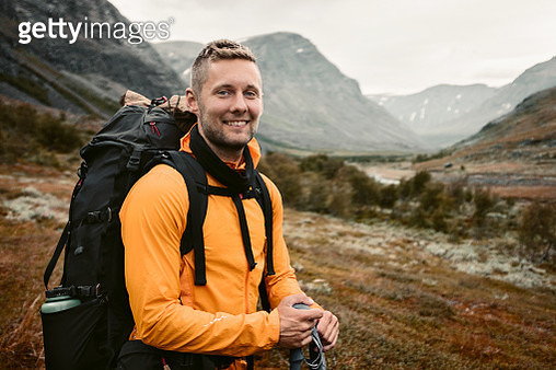 Smiling man carrying backpack in mountains - gettyimageskorea
