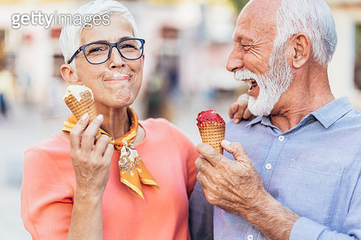 Modern and happy senior couple eating ice cream outdoor - gettyimageskorea