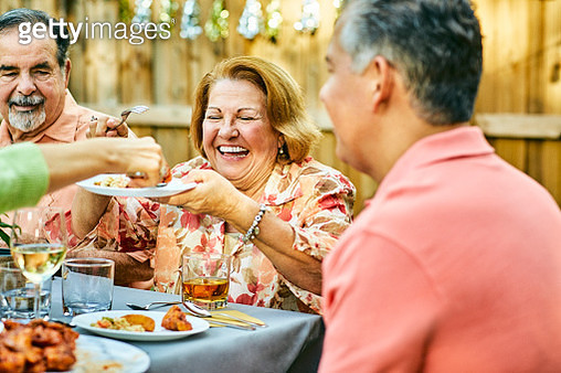 Cheerful family eating at table in back yard - gettyimageskorea