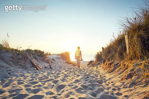 Lone female walking away from the beach on sandy path - gettyimageskorea