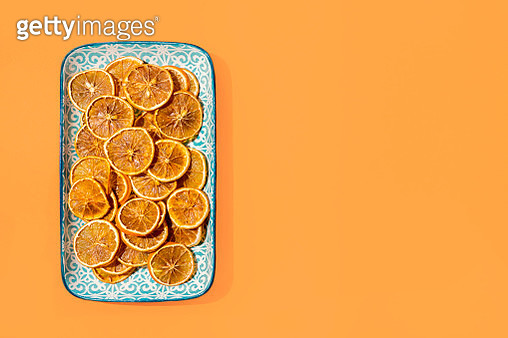 Directly above view of many dried orange slices on a plate. Orange background with copy space - gettyimageskorea