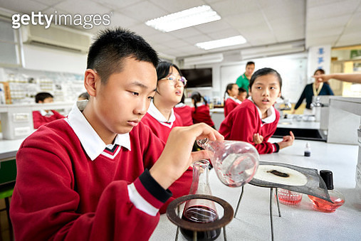 Focused teenage boy mixing liquid in laboratory flask. Teachers are teaching students in chemistry class. They are learning science. - gettyimageskorea