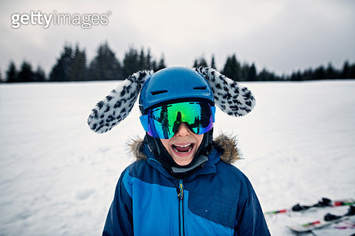 Little skier aged 9 is enjoying skiing on a winter day. The boy wearing cool helmet with ears is smiling into the camera.  Cold winter day. Nikon D850 - gettyimageskorea