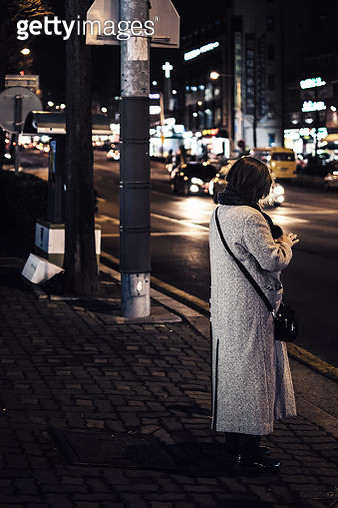 Mature woman using smartphone in sidewalk - gettyimageskorea