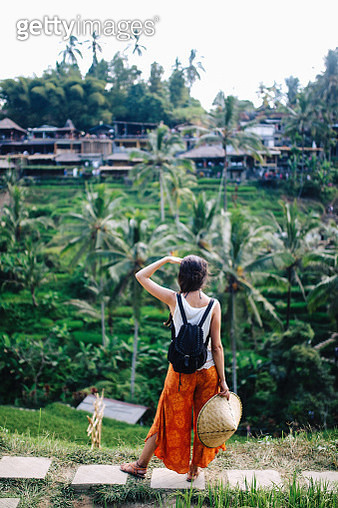 Young solo traveler woman is enjoying the amazing view above the rice terraces, fields in Bali, Indonesia. Tourism, traveling concepts in Southeast Asia, Indonesian culture. - gettyimageskorea