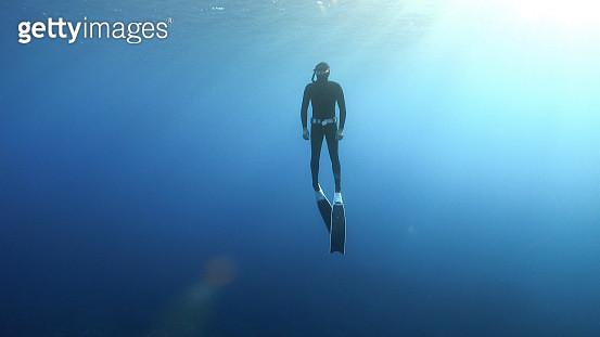 Deep sea diver swims underwater - gettyimageskorea