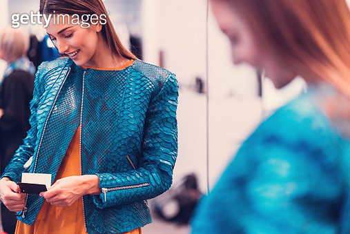 Smiling woman in the boutique measuring a leather jacket - gettyimageskorea