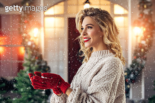 Beautiful girl enjoys Christmas snow beside her house - gettyimageskorea