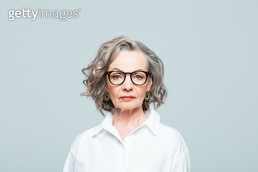 Elderly lady wearing white shirt and glasses standing against grey background, looking at camera. Studio shot of female designer. - gettyimageskorea