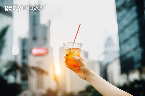 Human hand raised and holding up iced drink to the sky against urban city skyline - gettyimageskorea