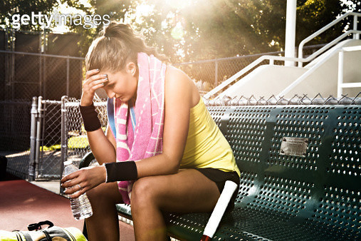 Female tennis player on bench with head in hands - gettyimageskorea