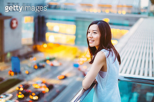 Young Asian girl leaning by the rooftop terrace enjoying the city view of Hong Kong - gettyimageskorea