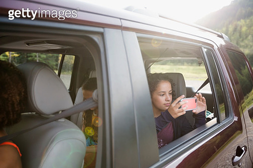 Girl using camera phone at window in back seat of SUV - gettyimageskorea