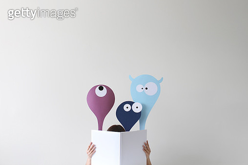 Woman reading book with friendly monsters popping up - gettyimageskorea