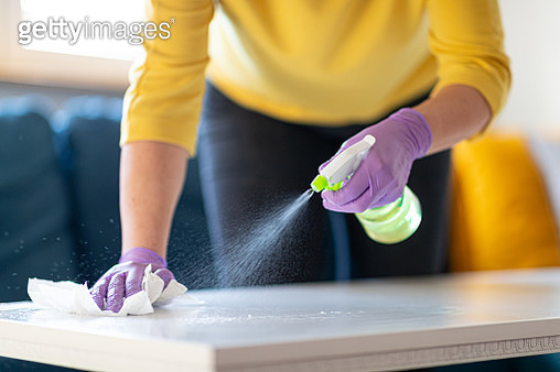 Hands in gloves disinfecting coffee table - gettyimageskorea