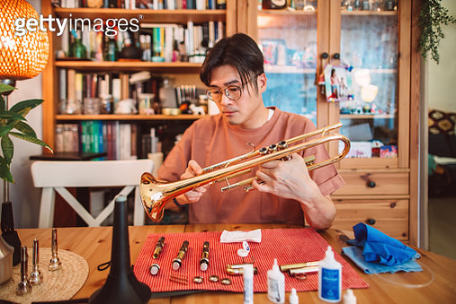 Young Asian man carrying out maintenace work of his trumpet at home - gettyimageskorea
