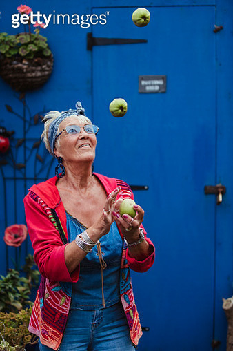 Senior woman standing juggling apples smiling. She is wearing all blue denim and blue tinted glasses with a blue door potting shed behind her. - gettyimageskorea