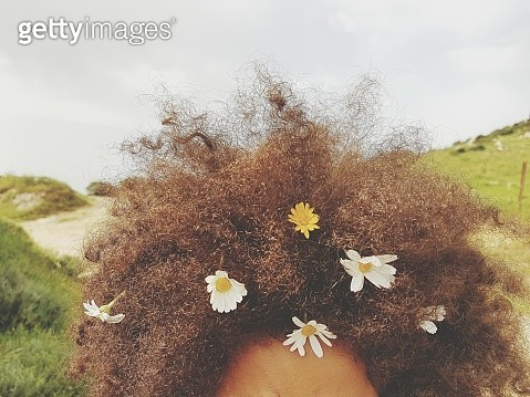 Cropped Image Of Flowers On Curly Hair - gettyimageskorea