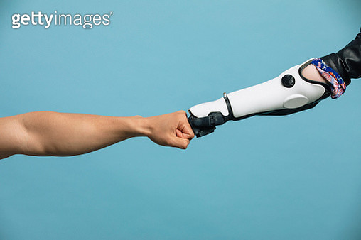 A Human and Robotic Arm Making a Fist Bump - gettyimageskorea