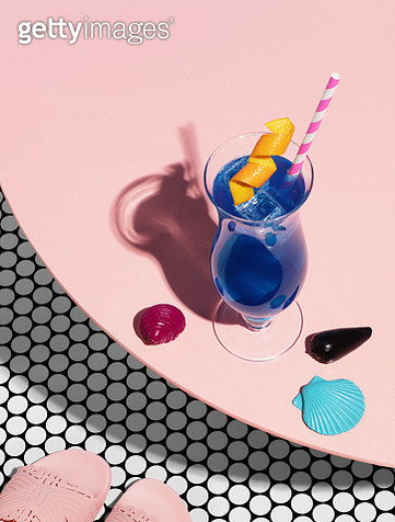 Still life image of blue cocktail in tall hurricane glass with straw and orange twist garnish standing on a table with beach slides. - gettyimageskorea