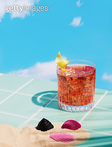 Still life image of a cocktail in a low tumbler glass with lemon twist garnish standing on tiled surface with sky background. - gettyimageskorea