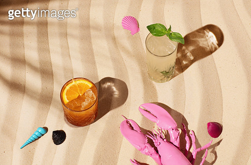 Still life image of a mezcal cocktail with flame and a mojito standing on a sandy beach with a pink lobster and seashells. - gettyimageskorea