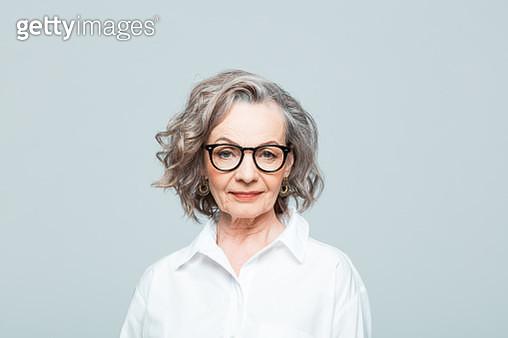 Elderly lady wearing white shirt and glasses standing against grey background, smiling at camera. Studio shot of female designer. - gettyimageskorea